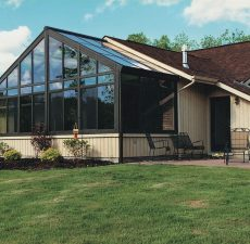 Glass cathedral sunroom next to a patio