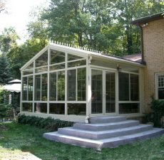 Glass cathedral sunroom with cement steps to outside