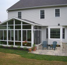 solid roof cathedral sunroom off of outdoor patio