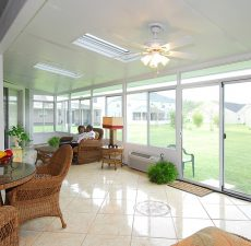 Couple enjoying time in solid straight roof sunroom installation